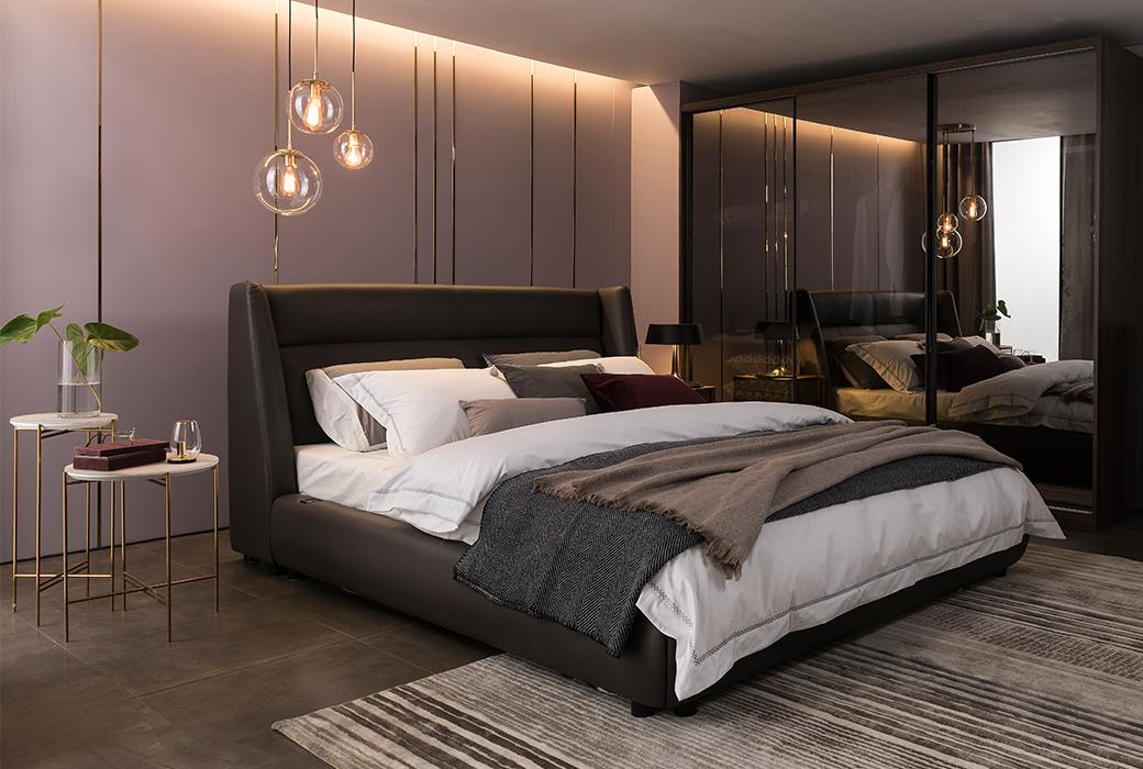 차콜그레이 컬러의 아인슈페인 침대가 침실 가운데 놓여있고 화이트 컬러의 매트리스와 이불, 베개가 있습니다