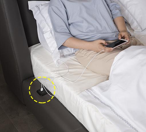 침대 위에 사람이 헤드보드에 등을 기다고앉아 침대 프레임 사이드 측면에 탑재된 USB 포트에 핸드폰 충전 케이블을 꽂고 핸드폰을 충전하고 있는 모습