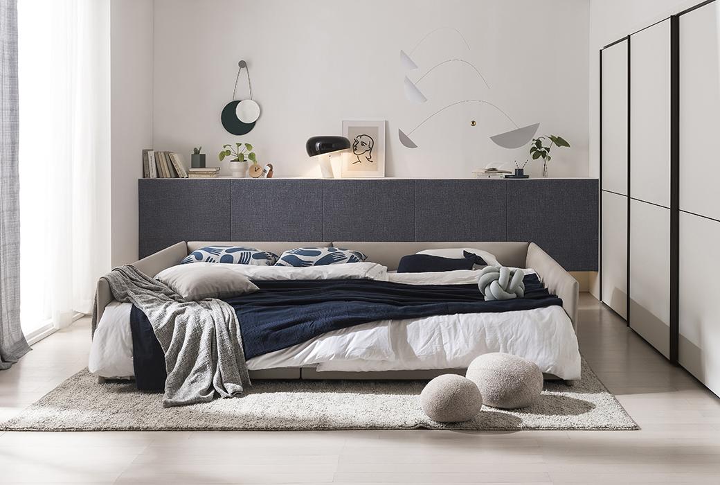 코튼 베이지 컬러의 당케 침대 위에는 네이비, 화이트, 그레이 컬러의 이불과 베개가 놓여져 있습니다