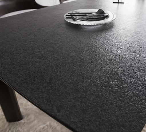 클로즈업 된 블랙컬러의 화산석 상판은 오돌토돌한 텍스처 질감이 가미되어 있고 식탁 위에는 접시가 놓여져 있습니다