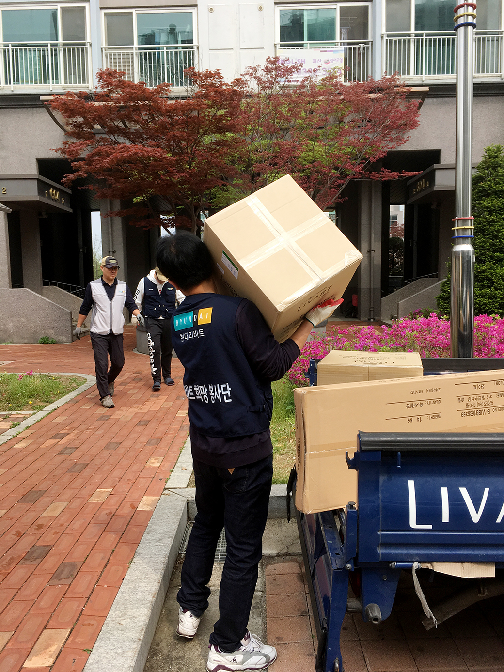 리바트 희망 봉사단들이 지역아동센터에 기증된 물건들을 트럭에서 내리는 모습.